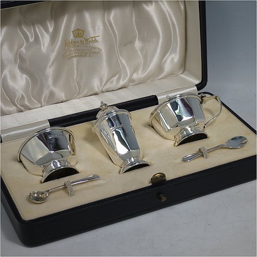 A Sterling Silver three-piece condiment set, in a panelled Art Deco style, and consisting of a pepper pot, open salt cellar, and covered mustard pot, the latter two items with original blue glass liners, and sitting on pedestal feet, the pepper pot with a pull-off lid with finial, and together with two silver condiment spoons, and all in their original cream satin & velvet-line presentation box. Made by Mappin & Webb of Birmingham in 1930 (the spoons being made in 1902). The dimensions of this fine hand-made silver condiment service are height of pepper pot 7 cms (2.75 inches), length of mustard pot 6.5 cms (2.5 inches), and the total weight is approx. 89g (2.9 troy ounces).