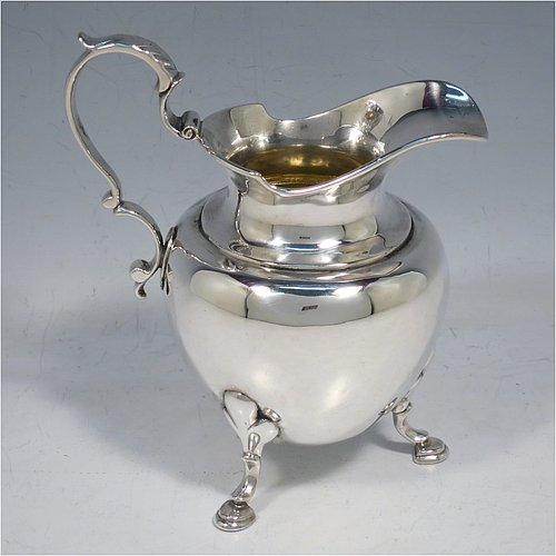 An Antique early Victorian Sterling Silver cream or milk  jug having a plain round bellied body, a cast scroll handle with anthemion leaf thumb-piece, a light gold-gilt interior, a shaped border with spout, and sitting on three cast hoof feet with shell shoulders. Made by Charles Gordon of London in 1837. The dimensions of this fine hand-made antique silver cream jug are height 14 cms (5.5 inches), length 12 cms (4.75 inches), and it weighs approx. 220g (7 troy ounces).