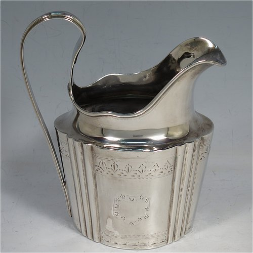 An Antique Georgian Irish Sterling Silver large cream jug, having a shaped oval body with hand-chased fluted corners and hand-engraved bands of floral work, an applied reeded border, a scroll handle, and sitting on a flat base. Made by William Williamson Dublin in ca. 1770. The dimensions of this fine hand-made antique Irish silver cream jug are height 14 cms (5.5 inches), length 11.5 cms (4.5 inches), and it weighs approx. 162g (5.2 troy ounces).