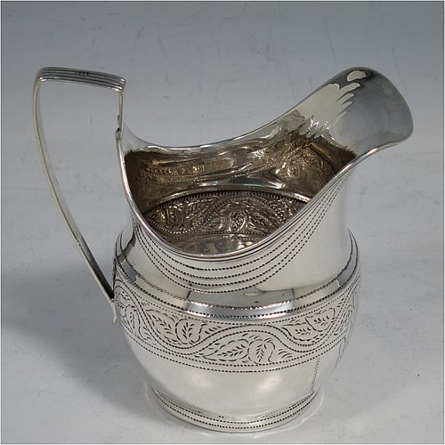 An Antique Victorian Sterling Silver cream jug, having a round baluster body with hand-chased stipple and floral work, an applied reeded border and reeded scroll handle, all sitting on a flat base. Made in Birmingham in 1889. The dimensions of this fine hand-made antique silver cream jug are height 8.5 cms (3.3 inches), length 10 cms (4 inches), and it weighs approx. 90g (2.9 troy ounces).