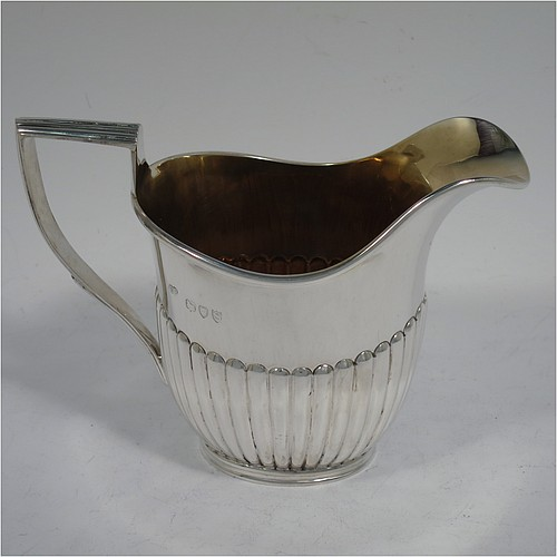 An Antique Victorian Sterling Silver cream jug in a Queen Anne style, having a body with hand-chased half-fluted decoration, a reeded handle and applied reeded border, a gold-gilt interior, and all sitting on a collet foot. Made by Charles Boyton of London in 1893. The dimensions of this fine hand-made antique silver cream jug are height 10 cms (4 inches), length 13.5 cms (5.3 inches), and it weighs approx. 150g (4.8 troy ounces).