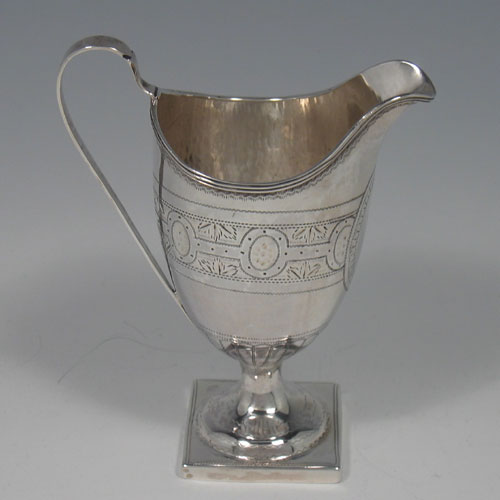 Antique Georgian sterling silver cream jug, having a round body with tapering sides in a Helmet style, with bands of floral decoration, a vacant cartouche, an applied reeded border, a scroll handle, and sitting on a pedestal foot with a square base. Made by Samuel Adams of London in 1799. The dimensions of this fine hand-made silver cream jug are length 11 cms (4.25 inches), height 12 cms (4.75 inches), and it weighs approx. 93g (3 troy ounces).