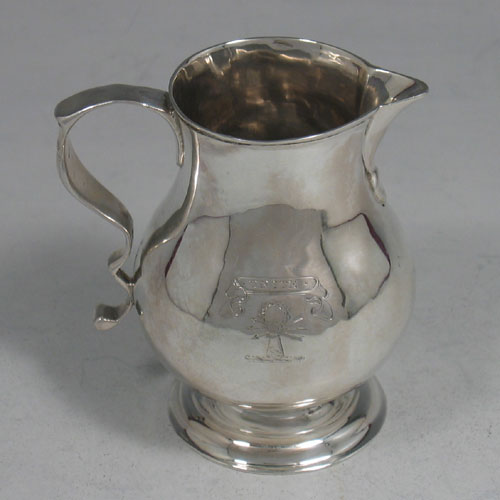 Antique Georgian sterling silver crested cream jug, made by George Greenhill Jones of London in 1738. Height 7 cms.