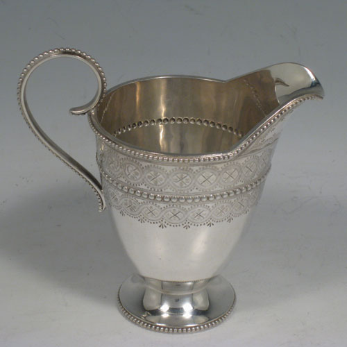 Antique Victorian sterling silver cream jug, having a round tapering body, with hand-engraved bead-work decoration, applied bead borders, a scroll handle, and sitting on a pedestal foot. Made by Edward Hutton of London in 1887. The dimensions of this fine sterling silver cream jug are height 10 cms (4 inches), length 11.5 cms (4.5 inches), and it weighs approx. 109g (3.5 troy ounces).