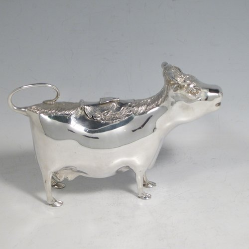 Sterling silver Cow cream jug, in a George II Cow creamer style, having a hinged lid with hand-chased flowers and an applied model of a bee, with a handle made from from the cows looped tail, and a spout made from the cows mouth, all sitting on four hoof feet! Made by Garrards & Co. Ltd., of London in 1978. The dimensions of this fine hand-made silver cow creamer are length 15 cms (6 inches), height 10 cms (4 inches), and it weighs approx. 152g (5 troy ounces).