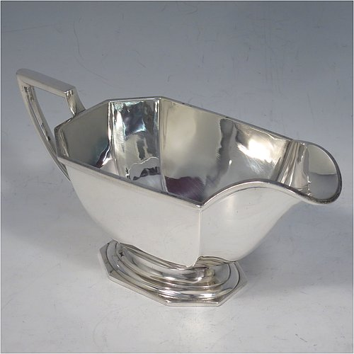 A Sterling Silver Art Deco style sauce or gravy boat, having a plain octagonal panelled body, with an applied reeded border, an angular handle, and sitting on a matching pedestal foot. Made by the Barker Brothers of Birmingham in 1936. The dimensions of this fine hand-made silver sauce boat are length 18 cms (7 inches), width 8 cms (3inches), height 8 cms (3 inches), and it weighs 248g (8 troy ounces).