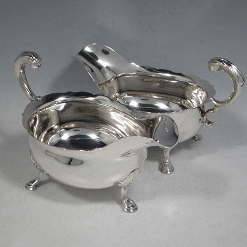 Antique Georgian sterling silver pair of large sauce or gravy boats, having plain baluster bodies, Chippendale borders, cast scroll handles, and sitting on three cast hoof feet with shell shoulders. Made by Thomas Cooke II and Richard Gurney of London in 1753. The dimensions of these fine hand-made antique silver sauce boats are length 18 cms (7 inches), width 10 cms (4 inches), height 11.5 cms (4.5 inches), and they weigh a total of 495g (16 troy ounces).