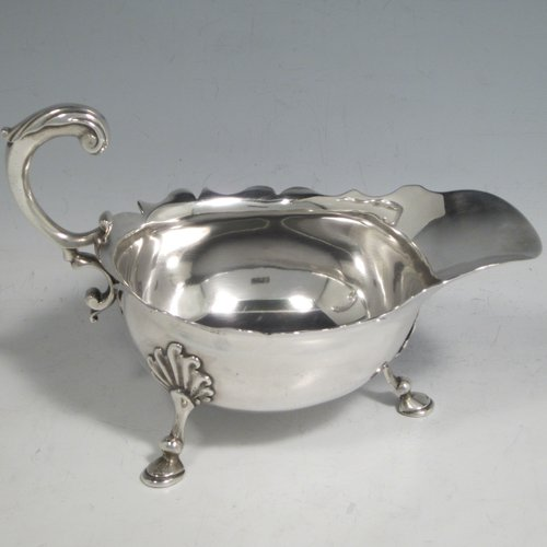 Antique Georgian sterling silver George II sauce or gravy boat, having a plain baluster body, with a Chippendale border, cast scroll handle, and sitting on three cast hoof feet with shell shoulders. Made by Robert Albin Cox (poss.) of London in 1753. The dimensions of this fine hand-made antique silver sauce boat are length 19 cms (7.5 inches), width 8.3 cms (3.3 inches), height 11 cms (4.25 inches), and it weighs 264g (8.5 troy ounces).