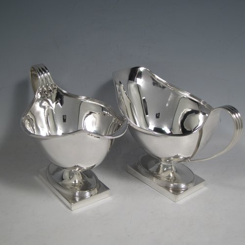Antique sterling silver pair of large sauce or gravy boats, having plain oval baluster bodies, applied reeded borders, reeded loop handles, and sitting on pedestal feet with rectangular bases. Made by Hawksworth & Eyre Co. Ltd., of London in 1911. The dimensions of these fine hand-made antique silver sauce boats are length 18.5 cms (7.25 inches), width 11 cms (4.25 inches), height 12.5 cms (5 inches), and they weigh a total of 650g (21 troy ounces).