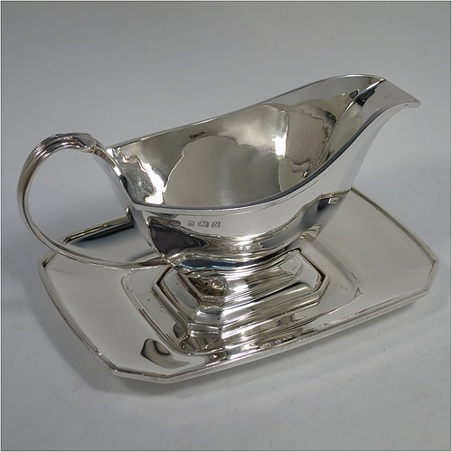 A Sterling Silver Art Deco style sauce or gravy boat on original stand, having a plain panelled body, with an applied reeded border, a scroll handle, sitting on an octagonal pedestal foot, and an original octagonal panelled drip stand. Made by the Adie Brothers of Birmingham in 1937. The dimensions of this fine hand-made Art Deco silver gravy or sauce boat and stand are length 18 cms (7 inches), width of stand 13 cms (5 inches), height 10 cms (4 inches), and it weighs a total of 430g (13.8 troy ounces).