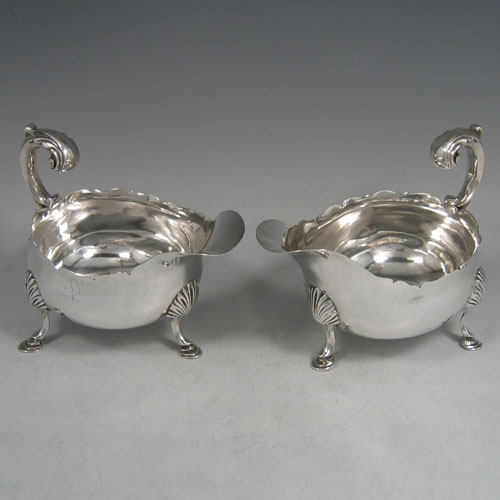 Antique Georgian sterling silver pair of sauce or gravy boats, having plain baluster bodies, chippendale borders, cast scoll handles, and sitting on three cast hoof feet with shell shoulders. Made by William Shaw II of London in 1765. The dimensions of these fine hand-made pair of antique silver sauce boats are length 16 cms (6.25 inches), width 10 cms (4 inches), height 11.5 cms (4.5 inches), and they weigh a total of 568g (18.3 troy ounces). Please note that these are crested.