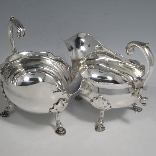 Antique Georgian sterling silver pair of sauce or gravy boats, having plain baluster bodies, Chippendale borders, cast scroll handles, and sitting on three cast hoof feet with shell shoulders. Made by William Smith I of London in 1761. The dimensions of these fine hand-made antique silver sauce boats are length 15 cms (6 inches), width 8.3 cms (3.3 inches), height 11.5 cms (4.5 inches), and they weigh a total of 405g (13 troy ounces).