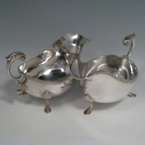 Sterling silver pair of heavy George II style sauce boats with gadroon edges, scroll handles, and sitting on three hoof feet with shell shoulders. Made by Wakely and Wheeler of Sheffield in 1991. Length 19 cms (7.5 inches), height 10 cms (4 inches), width 10 cms (4 inches). Total weight approx. 25 troy ounces (775g).