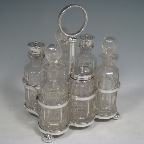 Antique Victorian sterling silver cruet set, having a plain stand with ring handle and frame for six hand-cut crystal cruet bottles with original stoppers and silver mounts, all sitting on a base with four cushion feet. Made by William Hutton and Sons of Sheffield in 1901. Height 22 cms (8.75 inches), length 16.5 cms (6.5 inches), width 13 cms (5 inches). Total weight approx. 650g (21 troy ounces).