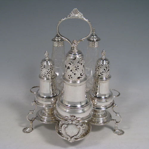 Antique Georgian sterling silver and hand-cut crystal five-bottle Warwick style cruet set, having a stand with scroll work holders, a cast and twisted loop handle, a cast applied cartouche and sitting on four cast shell feet. With two smaller baluster style pepper pots, a larger caster, and two crystal shakers with silver tops. Made by Jabez Daniel and James Mince of London in 1767. The dimensions of this fine hand-made silver cruet set are width of stand 19 cms (7.5 inches), height of stand 23 cms (9 inches), and weight of silver approx. 770g (24.8 troy ounces). Please note that the silver tops on the crystal bottles are unmarked, and the stand is crested.