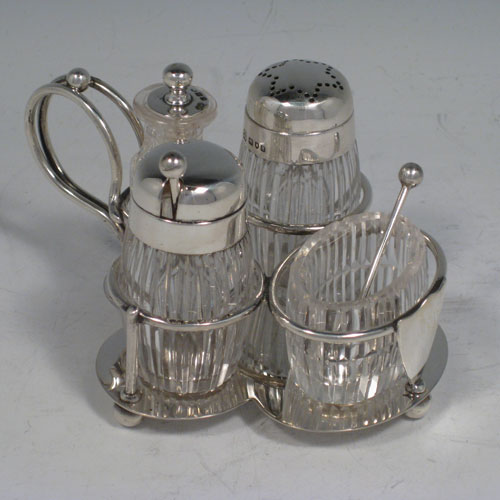 Antique Victorian sterling silver and hand-cut crystal small cruet set with open salt and spoon, mustard pot with lid and spoon, pepper pot with removable lid, and a chilli sauce pot with attached spoon. All sitting inside a wire-work frame with scroll handle and plain base sitting on four ball feet. All spoons are original. Made by Heath and Middleton of London in 1896. Length 12 cms (4.75 inches), width 9.5 cms (3.75 inches), height 7 cms (2.75 inches).