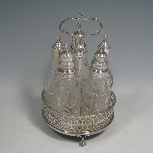 Antique Georgian sterling silver and hand-cut crystal five-bottle cruet set, having a stand with hand-pierced gallery, gadroon edge border, a cast and pierced loop handle, and sitting on four cast claw and ball feet. Made by Jabez Daniel and James Mince of London in ca. 1770. The dimensions of this fine hand-made silver cruet set are diameter of stand 13.5 cms (5.25 inches), height 21.5 cms (8.5 inches), and weight of stand approx. 300g (9.6 troy ounces). Please note that the silver tops on the crystal bottles are unmarked, and the stand is crested.
