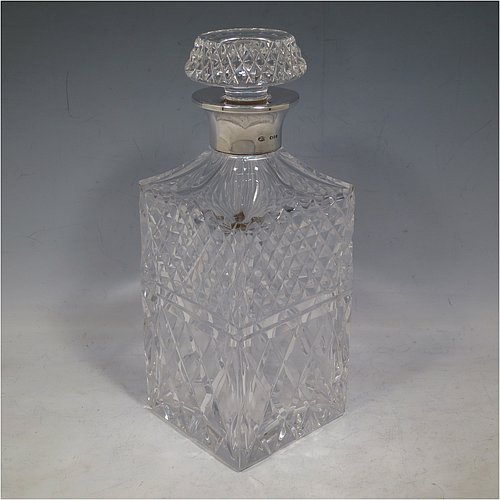 A Sterling Silver and hand-cut crystal decanter, having a square cross-section body with straight sides and hand-cut hobnail decoration, a plain silver collar, and original hand-cut stopper. Made in London in 1969, by I. Freeman & Sons Ltd. The dimensions of this fine hand-made silver and crystal decanter are height 23 cms (9 inches), and 9 cms (3.5 inches) square.