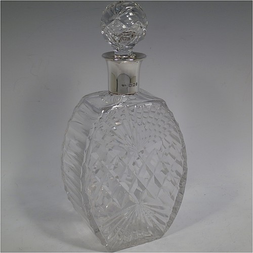 A very unusually designed Sterling Silver and hand-cut crystal decanter, having a main oval body at front and back with hobnail and star-burst cut, and with tapering sides having stepped decoration, a plain silver collar, an original hand-cut stopper, and sitting on a flat base with a matching star-cut. Made by Mappin and Webb of Sheffield in 1956. The dimensions of this fine hand-made silver and crystal decanter are height 25.5 cms (10 inches), width 12 cms (4.75 inches), and depth at base 7 cms (2.75 inches).