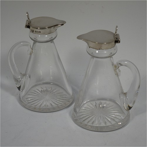 A Sterling Silver pair of whisky toddies or noggins, having round based hand-cut crystal bodies with tapering sides and loop handles, mounted with silver collars and hinged flat lids with thumb-pieces, all sitting on flat star-cut bases. Made by Goldsmiths and Silversmiths of London in 1932. The dimensions of this fine hand-made pair of silver and crystal noggins or toddies are height 11 cms (4.25 inches), and diameter at bases 6.5 cms (2.5 inches).