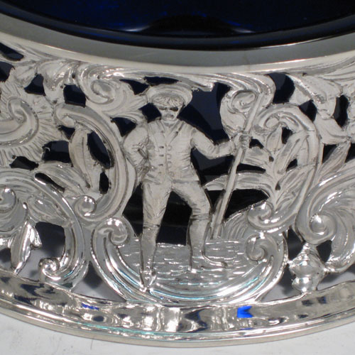 Antique Victorian sterling silver dish ring, having a hand-pierced and chased body with floral and figural decoration, and with a blue-glass liner bowl. Made by D & J Wellby of London in 1897. Diameter 18 cms (7 inches), height 7.5 cms (3 inches). Weight approx. 387g (12.5 troy ounces).