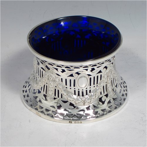 An Antique Edwardian Sterling silver miniature dish ring, having a hand-pierced and chased body with neoclassical style decoration, and a blue-glass liner. Made by Williams of Birmingham in 1910. The dimensions of this fine hand-made miniature silver dish ring are height 8 cms (2.3 inches), diameter at base 10 cms (4 inches), and it weighs approx. 85g (2.7 troy ounces).