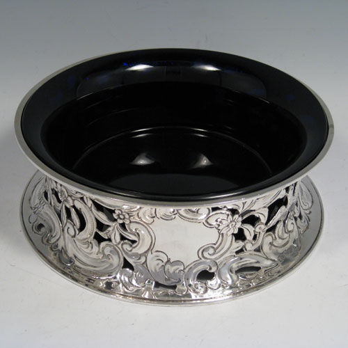 Antique Edwardian sterling silver dish ring, having a hand-chased and pierced body with floral and figural decoration, and with a blue-glass liner bowl. Made by James Parkes of London in 1908. Diameter 20 cms (8 inches), height 7 cms (2.75 inches). Weight approx. 420g (13.5 troy ounces).