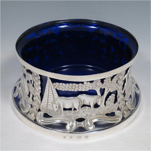 An Antique Edwardian Sterling Silver large table dish ring in an Irish style, having a hand-pierced and chased body decorated with pastoral scenes, figures, and animals, and a blue-glass liner. Made by Israel Sigmund Greenberg of Birmingham in 1904. The dimensions of this fine hand-made antique silver dish ring are height 10 cms (4 inches), diameter at base 20 cms (8 inches), and it weighs approx. 387g (12.5 troy ounces).