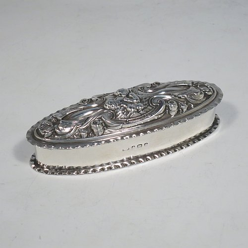 A very pretty Antique Edwardian Art Nouveau Sterling Silver dressing table box, having an oval body with crimped borders, a hinged lid with hand-chased floral, scroll, and Cherub work, and sitting on a flat base. Made by Levi & Salamon of Birmingham in 1902. The dimensions of this fine hand-made silver dressing table box are length 11 cms (4.25 inches), width 4 cms (1.5 inches), height 3 cms (1.25 inches), and it weighs approx. 165g (2 troy ounces).