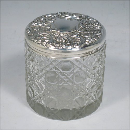 An Antique Victorian Sterling Silver and cut-crystal dressing table jar / box, having a round hand-cut crystal body in the Hobnail pattern, a hand-chased pull-off lid with floral decoration, and sitting on a flat star-cut base. Made by Adie & Lovekin Ltd., of Birmingham in 1901. The dimensions of this fine hand-made antique silver and crystal dressing table box / jar are height 8 cms (3 inches), and diameter 7 cms (2.75 inches).