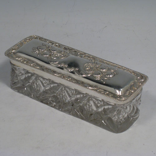Antique Edwardian sterling silver and crystal dressing table jar / box, having a pull-off lid with hand-chased floral decoration, and a rectangular hand-cut crystal body. Made in Birmingham in 1906. Length 12 cms (4.75 inches), width 4.5 cms (1.75 inches), height 4 cms (1.5 inches).