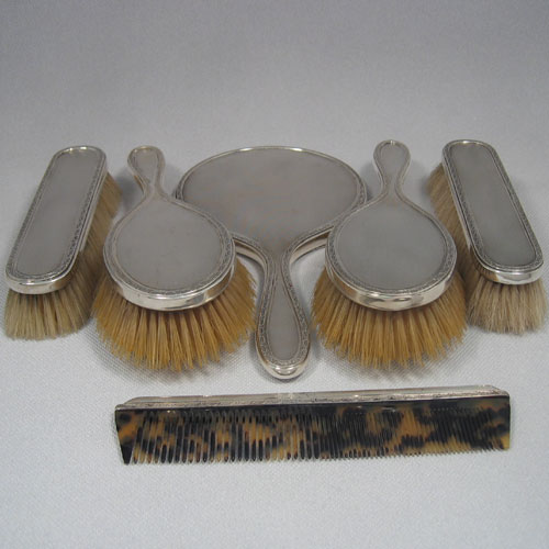 Sterling silver six-piece engine-turned dressing table set with bevelled hand mirror, two hair brushes, two clothes brushes, and a comb, having pretty floral borders. All made by Robert comyns of London in 1935. Length of mirror 25 cms.
