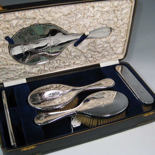 Sterling silver five-piece dressing table set in its original satin and blue-velvet lined box, with very pretty neoclassical style hand-engraving, and original bevelled mirror and pig-bristle brushes. All made by James Dixon & Sons of Sheffield in 1931. Length of hand mirror 28 cms (11 inches).