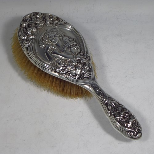 An Antique Edwardian Sterling silver Art Nouveau dressing table hair brush, having very pretty hand-chased floral and ribbon decoration, surrounding a figure of a lady. All with original bristles and wooden mount in very good condition. Made by Henry Miller of Birmingham in 1903. The dimensions of this fine hand-made hair brush are length 24 cms (9.5 inches), and width 9 cms (3.5 inches).