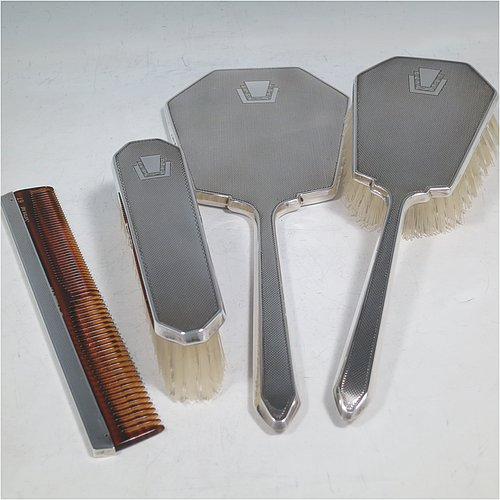 A Sterling Silver Art Deco style dressing table set with four pieces, consisting of a hand-mirror with original bevelled mirror, a clothes brush, a hair brush, all with original bristles, and an original comb, all with engine-turned decoration and vacant geometric Art Deco style cartouches. Made by the Daniel Manufacturing Co., of Birmingham in 1949. The dimensions of this fine hand-made sterling silver dressing table service are length of mirror 27 cms (10.5 inches), length of hair brush 22 cms (8.75 inches), and length of clothes brush 13.5 cms (5.3 inches).