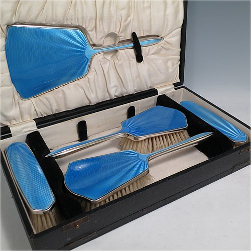 A Sterling Silver and light blue enamelled Art Deco style dressing table set with five pieces, consisting of a hand-mirror with original bevelled mirror, two clothes brushes, and two hair brushes, all with original bristles, and all in their original black velvet and cream satin-lined presentation box. Made by W. G. Sothers Ltd., of Birmingham in 1931. The dimensions of this fine hand-made sterling silver and enamelled dressing table service are length of hand mirror 26.5 cms (10.5 inches), length of hair brush 23.5 cms (9.25 inches), and length of clothes brush 14.5 cms (5.75 inches).