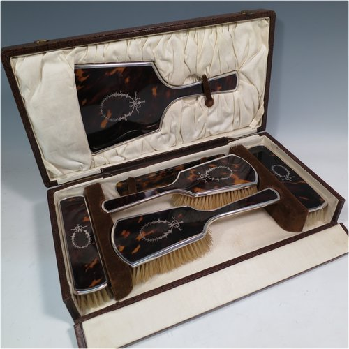 A Sterling Silver and inlaid tortoise-shell dressing table set with six pieces, consisting of a hand-mirror with original bevelled mirror, two clothes brushes, two hair brushes, all with original bristles, and a comb, all in original satin-lined presentation box. Made by Henry Matthews of Birmingham in 1924. The dimensions of this fine hand-made sterling silver and tortoiseshell dressing table service are length of mirror 27 cms (10.5 inches), and dimensions of box are length 37 cms (14.5 inches), width 19 cms (7.5 inches), and height 8.5 cms (3.3 inches). Please note that there is slight damage to the satin hinges.