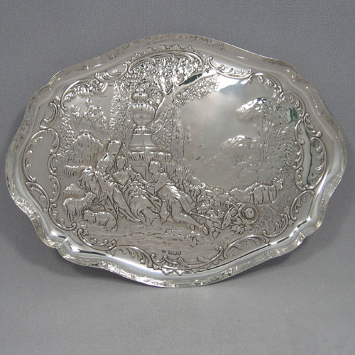 An Antique Edwardian Sterling Silver dressing table pin tray, having a shaped oval body with a raised edge border, and a hand-chased pastoral scene of figures reclining under a spreading oak tree, and all sitting on a flat base. Made by William Comyns of London in 1907. The dimensions of this fine hand-made antique silver pin or dressing table tray are length 31 cms (12 inches), width 23 cms (9 inches), and it weighs approx. 341g (11 troy ounces).