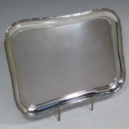 A pretty Antique Edwardian Sterling Silver dressing table tray, having a rectangular body with rounded corners, a plain ground, an applied laurel-leaf and reeded border, and all sitting on a flat base. Made by Harrison Brothers and Howson of Sheffield in 1910. The dimensions of this fine hand-made ique antsilver dressing table tray are length 30 cms (12 inches), width 22 cms (8.75 inches), and it weighs approx. 512g (16.5 troy ounces).