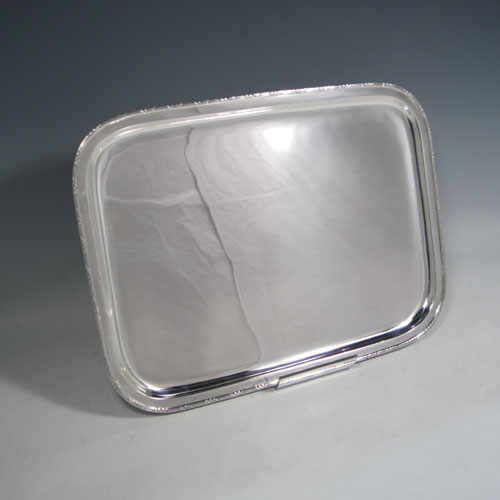 Antique Edwardian sterling silver dressing table tray, having a rectangular body with rounded corners, a plain ground, an applied laurel-leaf and reeded border, all sitting on a flat base. Made in London in 1909. The dimensions of this fine hand-made silver dressing table tray are length 33 cms (13 inches), width 24 cms (9.5 inches), and it weighs approx. 636g (20.5 troy ounces).