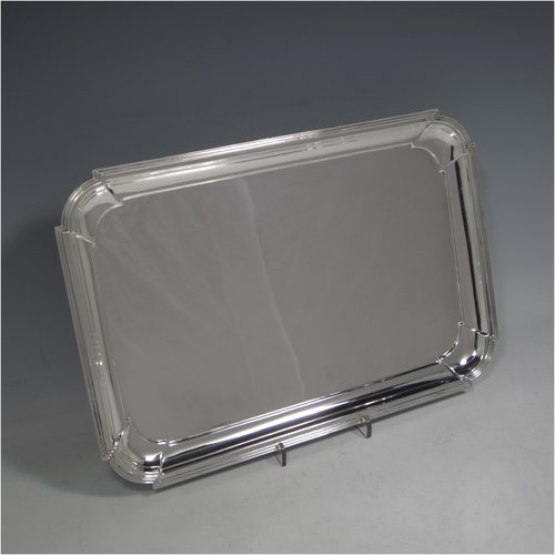 A Sterling silver Art Deco dressing table tray, having a rectangular body with cut corners, a plain ground, an applied reeded border, and  sitting on a flat base. Made by A. & J. Zimmerman of Birmingham in 1929. The dimensions of this fine hand-made silver dressing table tray are length 31 cms (12.75 inches), width 21 cms (8.25 inches), and it weighs approx. 495g (16 troy ounces).