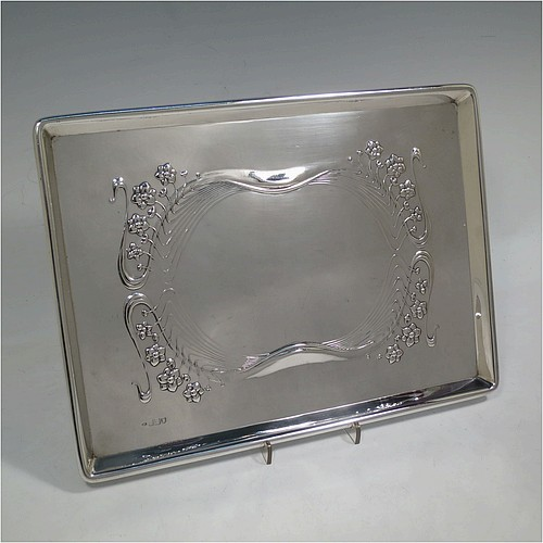 A very pretty Antique Edwardian Sterling Silver Art Nouveau style dressing table pin tray, having a rectangular body with hand-chased floral and ribbon work, a raised plain outer border, and all sitting on a flat base. Made by Charles H. Dumeril of London in 1907. The dimensions of this fine hand-made antique silver pin tray are length 32 cms (12.5 inches), width 23 cms (9 inches), and it weighs approx. 584g (18.8 troy ounces).