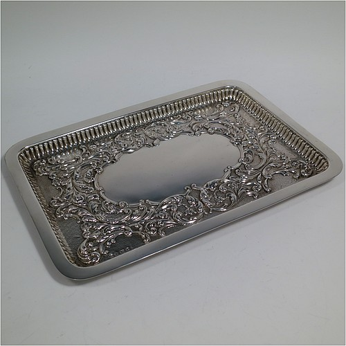 An Antique Edwardian Sterling Silver dressing table pin tray, having a rectangular body with a raised fluted border, hand-chased floral and scroll decoration on a hand-hammered ground, with a central vacant cartouche, and all sitting on a flat base. Made by William Aitken of Birmingham in 1909. The dimensions of this fine hand-made antique silver pin or dressing table tray are length 27 cms (10.5 inches), width 19 cms (7.5 inches), and it weighs approx. 216g (7 troy ounces).