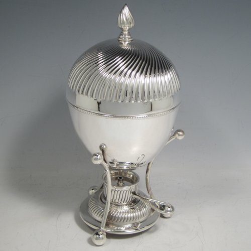 Antique Edwardian silver-plated egg coddler, having a plain round body, with lift-off lid having swirl fluting and a flame finial, and internal holder for four eggs, attached to a frame and stand with an original burner, all sitting on three ball feet. Made by Welbeck & Co., in ca. 1900. The dimensions of this fine hand-made silver plated egg coddler are height 23.5 cms (9.25 inches), and diameter 11 cms (4.3 inches).
