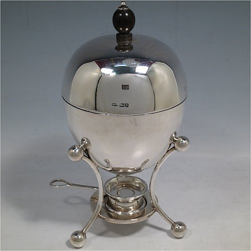 A rare Antique Edwardian Sterling Silver egg coddler, having a plain round body, with lift-off lid and wooden finial, sitting in a wire-work frame with ball terminals, an interior egg-holder for four eggs, and an original burner, all sitting on four ball feet. Made by Mappin & Webb of Sheffield in 1907. The dimensions of this fine hand-made antique silver egg coddler are height 23 cms (9 inches), diameter 11 cms (4.3 inches), and it weighs approx. 510g (16.5 troy ounces).