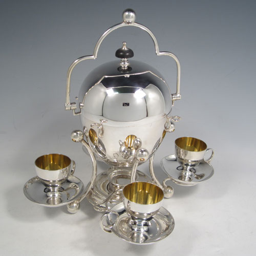 Antique Edwardian silver-plated egg coddler, having a plain round body with lift-off lid, sitting in a frame with swing handle, with four removable egg cups, an interior egg-holder, and an original burner, all sitting on four ball feet. Made in ca. 1900. The dimensions of this fine hand-made silver plated egg coddler are height 27 cms (10.5 inches), and width 26 cms (10.25 inches).