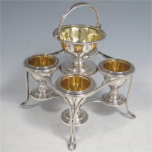 An Antique Georgian Sterling Silver egg cruet set, having four removable plain round egg cups, an unusual central condiment bowl for either salt or pepper with swing-handle, all with gold-gilt interiors, and all sitting in a wire-work frame stand with four feet. Made by Waterhouse, Hodson & Co., of Sheffield in 1828. The dimensions of this fine hand-made antique silver egg cruet set are height 18 cms (7 inches), width 17 cms (6.75 inches), with a total weight of approx. 530g (17 troy ounces).