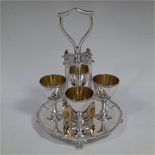 An Antique Victorian Sterling Silver egg cruet set, having four plain round egg cups with gold-gild interiors sitting on pedestal feet, four egg spoons with gold-gilt bowls, and a plain cast loop handle attached to a round base with an applied shaped gadroon border, and sitting on four cast scroll feet. Made by George Hancock of Sheffield in 1897 (the spoons by James Dixon and Sons of Sheffield in 1917). The dimensions of this fine hand-made antique silver egg cruet set are height 20 cms (8 inches), diameter of base is 15 cms (6 inches), and the total weight is approx. 688g (22 troy ounces).