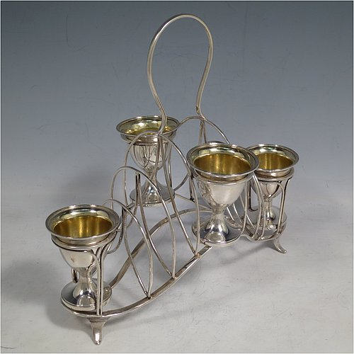 An Antique Georgian Sterling Silver egg cruet set, having four removable plain round egg cups with reeded borders and gold-gilt interiors, and all sitting in a wire-work frame toast-rack stand with four flange feet, and a looped carrying handle. Made by William Abdy of London in 1801. The dimensions of this fine hand-made antique silver egg cruet and toast set are height 22 cms (8.75 inches), length 23 cms (9 inches), width 14 cms (5.5 inches), with a total weight of approx. 500g (16 troy ounces).