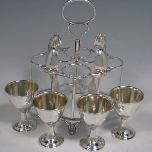Antique Victorian sterling silver egg cruet set, having four removable plain round egg cups with gold-gilt interiors, a wire-work frame stand sitting on four cast foliate feet, and four egg spoons in the Fiddle pattern. All pieces are part-crested with a leopards head. The stand and egg cups are all made by Joseph Angel of London in 1856, whilst the four spoons are made by John Stone of Exeter in 1854. Height 19 cms (7.5 inches), length 15 cms (6 inches). Total weight approx. 485g (15.6 troy ounces).